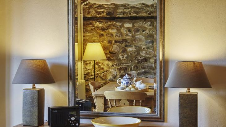 Beams and exposed stonework reflected in a mirror