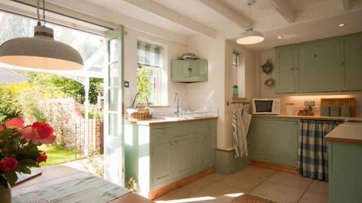 Country style kitchen with doors opening out to garden