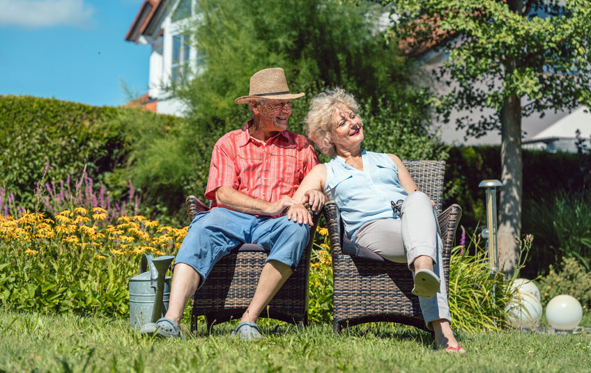 old people in their holiday cottage garden